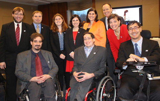 RespectAbility staff, fellows and board member smiling in a posed photograph. Three men and four women standing behind three men in wheelchairs. All are dressed formally in suits.