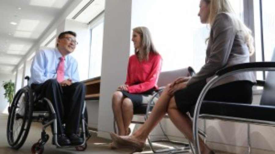 Won Shin, senior manager in transaction advisory services at EY, speaks with coworkers Alejandra Preciat and Frances Smith