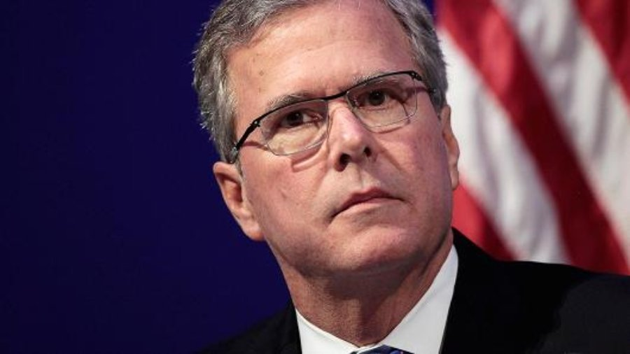 Jeb Bus looking at the camera wearing a suit in front of the American flag