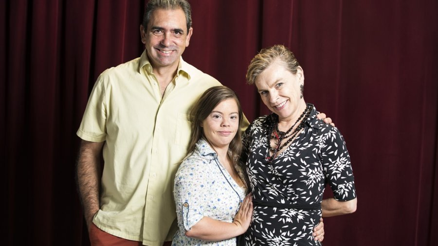 Cristina and her parents facing the camera and smiling with a red curtain behind them
