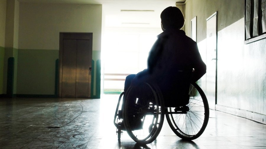 Individual in silhouette in a wheelchair in an empty hallway