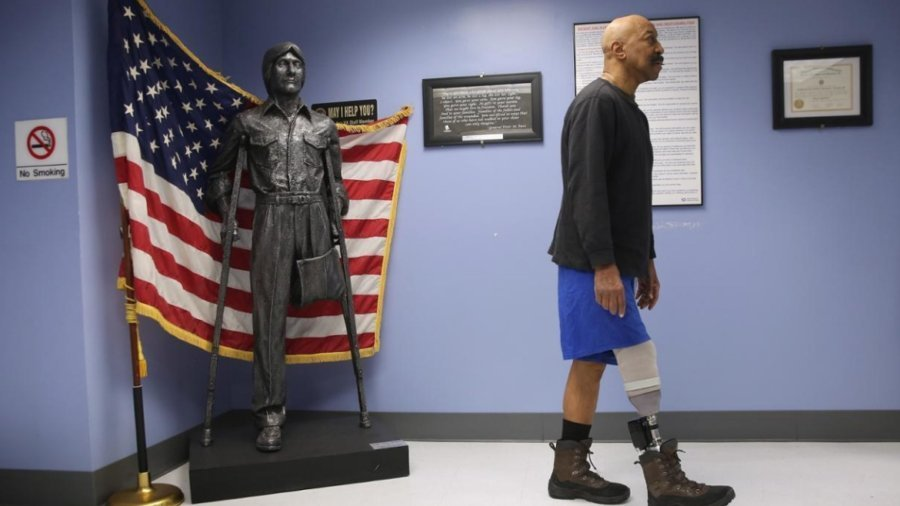 A veteran with a prosthetic leg walks past a statue with only on leg in front of an American flag