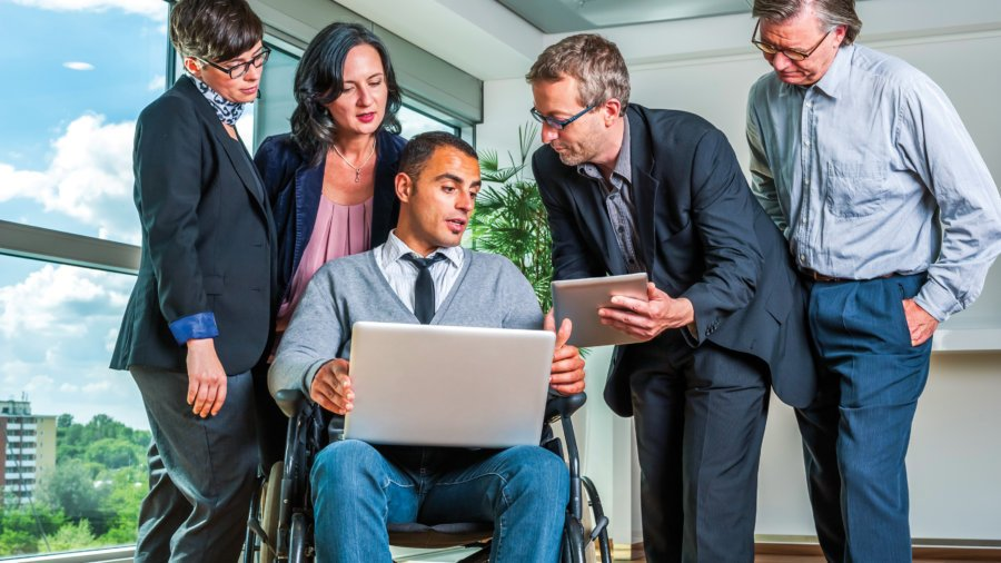 Five people - one in a wheelchair - looking at a computer in a business setting