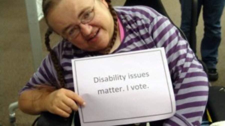"RespectAbility is asking all presidential candidates on both sides of the aisle to fill out a questionnaire and scorecard on disability issues. Image: Woman in wheelchair holding a sign that says: ""Disability issues matter. I vote."""