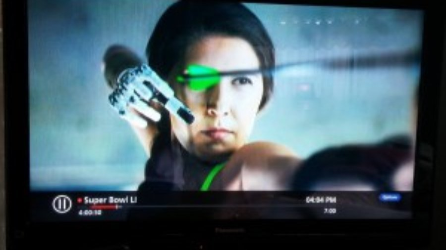 screenshot of ad: Angel Giuffria shooting a bow and arrow with her prosthetic arm and hand.