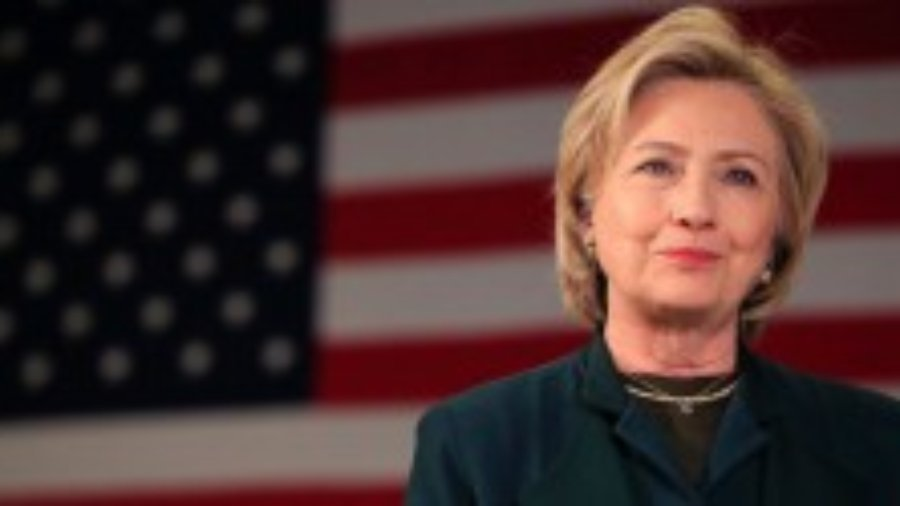 Hillary Clinton smiling with American flag as backdrop