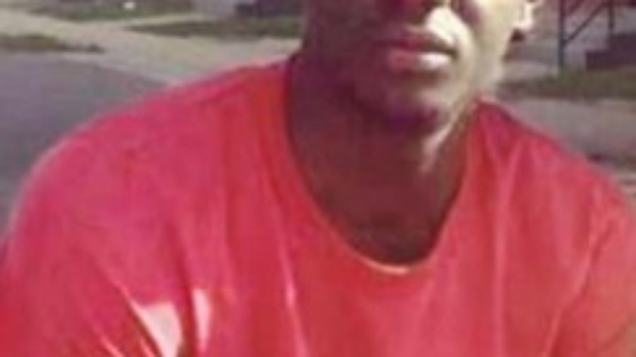 Headshot of Freddie Gray in a red t-shirt outside in front of homes