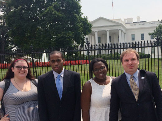 Four young professionals - a white woman, a Black man, a Black woman and a white man - dressed professionally in suits standing in front of the fence in front of the White House