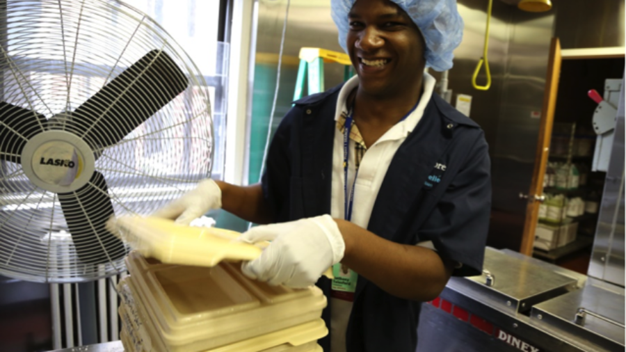 Image of man with hair net stacking trays in an industrial kitchen as example of #RespectTheAbility campaign
