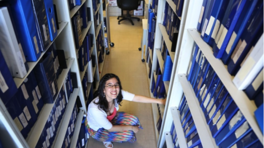 Young woman kneeling in a library organizing files
