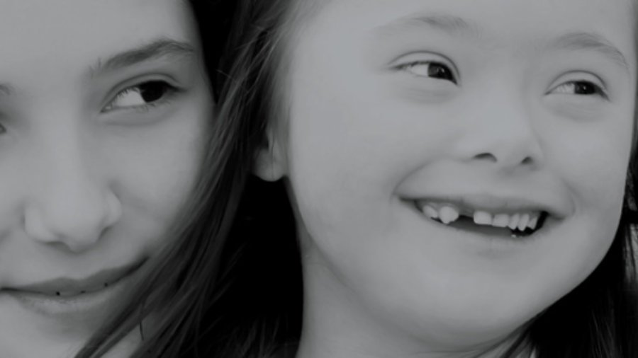 Image of two girls smiling and looking off into the distance.