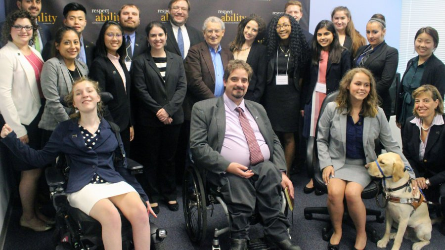 Stan Greenberg and RespectAbility Fellows standing and seated in a posed photograph, smiling for the camera