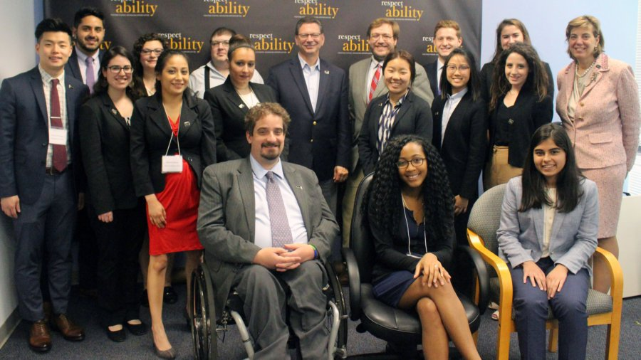 Steve Rakitt and RespectAbility Fellows standing and seated in a posed photograph, smiling for the camera