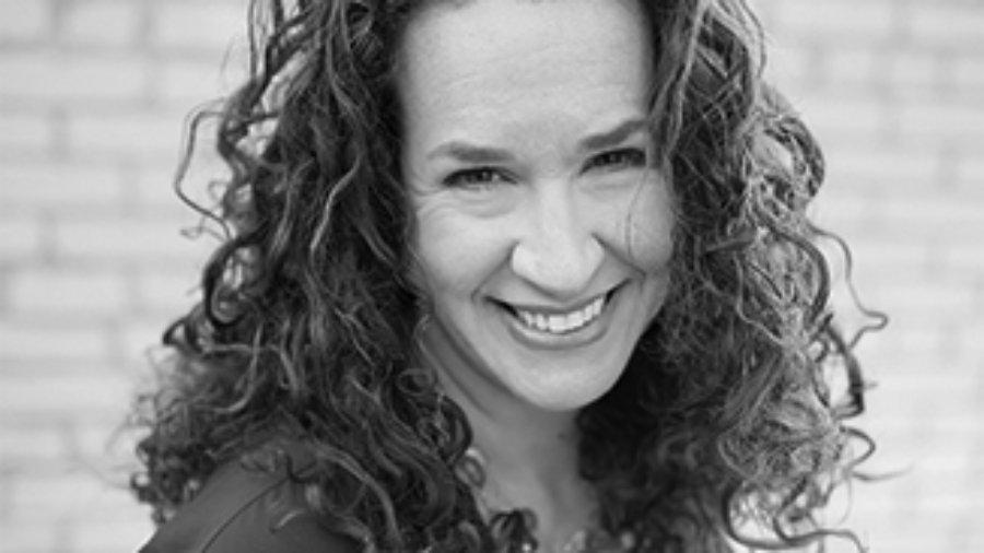 headshot of Dana Marlowe smiling at the camera she has long curly hair grayscale photo