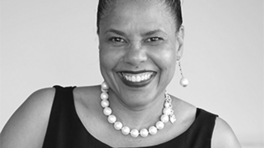 headshot of Donna Walton her hair is tied back and she is wearing a pearl necklace and pearl earrings, and smiling at the camera, grayscale photo