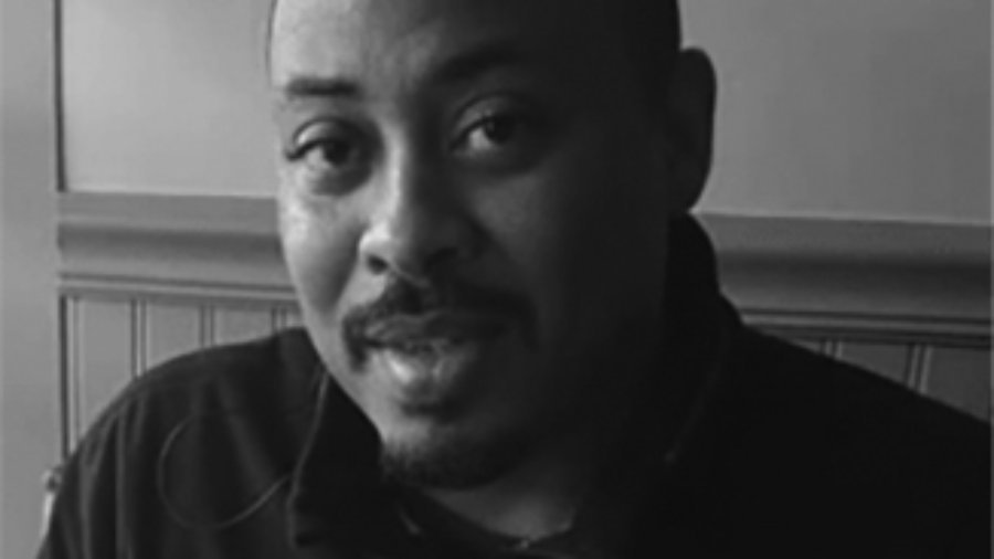 headshot of Eddie Ellis he is bald and he has a mustache grayscale photo