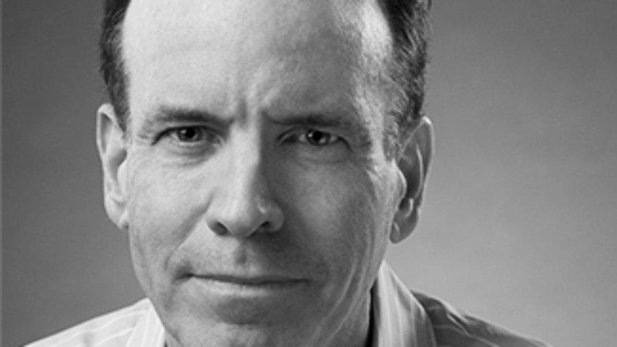 Headshot of Jonathan Murray wearing a striped shirt and facing the camera grayscale photo