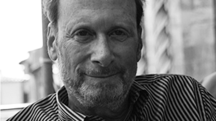 Robert Schwartz wearing a striped shirt and with a light beard and mustache grayscale photo