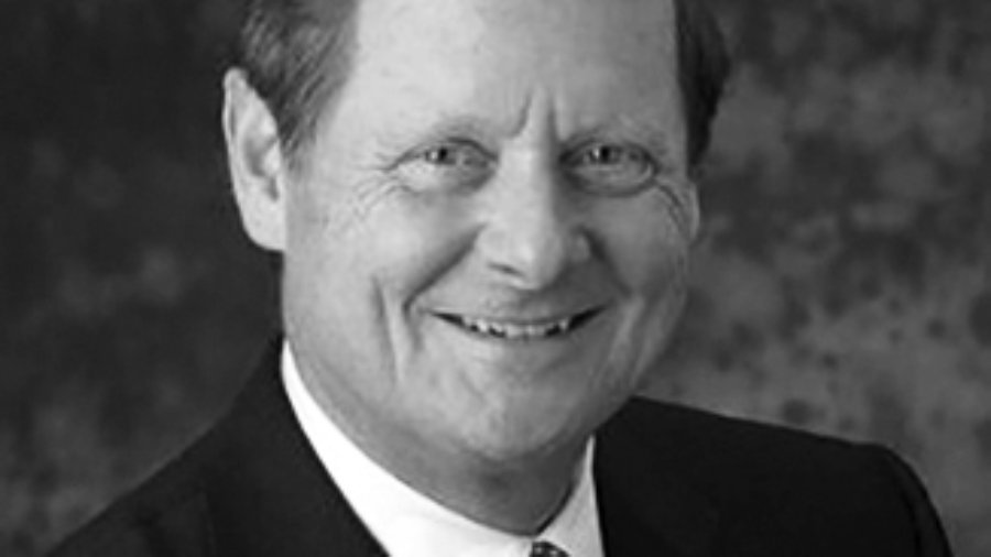 Steve Bartlett is smiling and wearing a black suit, white shirt, a spotted tie and an american flag pin on his jacket, grayscale photo