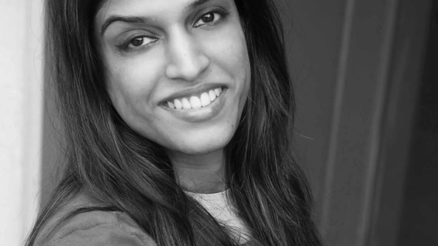 Headshot of Khadija Bari smiling leaning against a wall