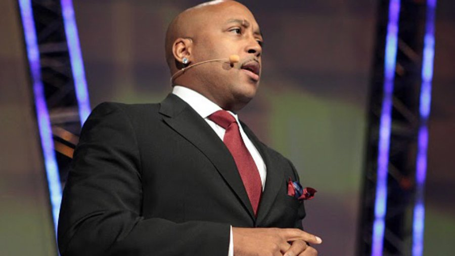 Daymond John in a black suit and red tie speaking into a microphone
