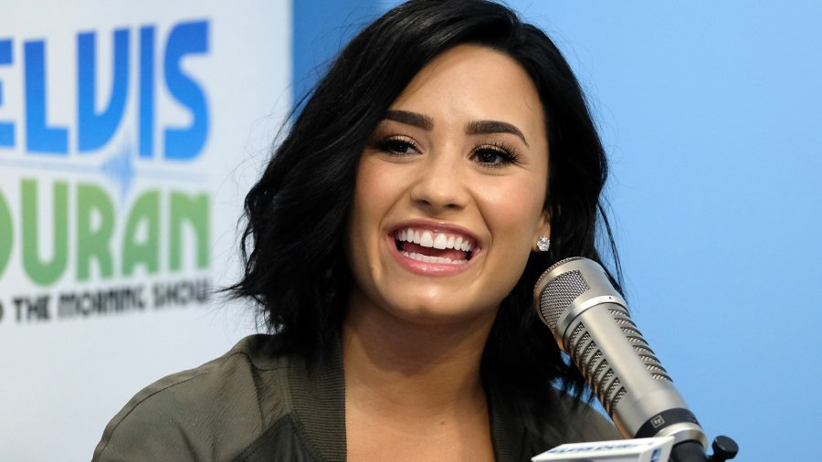 Demi Lovato smiling at a microphone