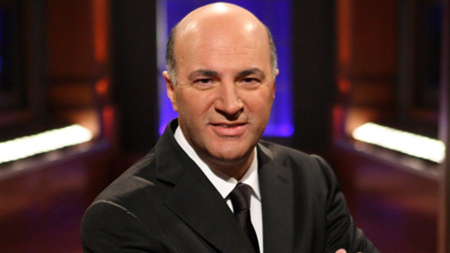 Kevin O'Leary posing for the camera wearing a black suit on the set of Shark Tank
