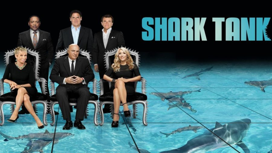 Shark Tank promo photo showing six main sharks seated and standing above a shark tank with the words