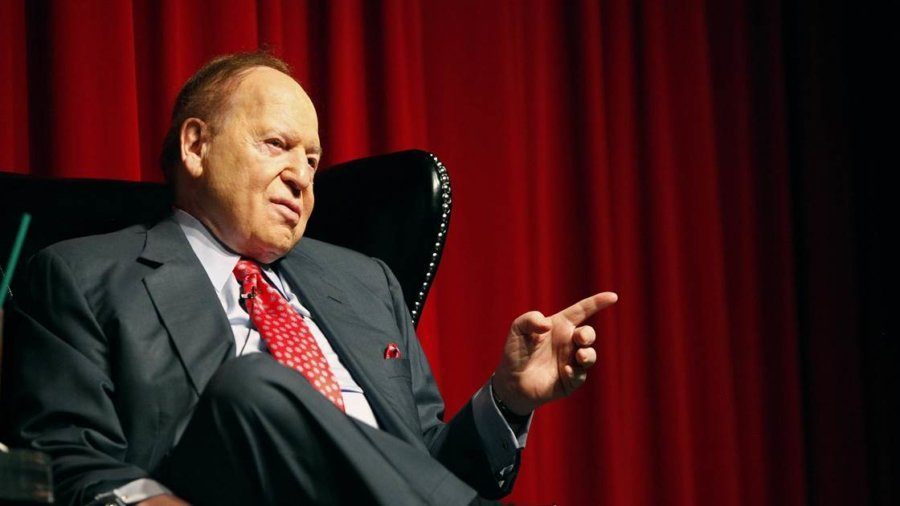 Sheldon Adelson seated in a gray suit and red tie, pointing to the left, with red drapes behind him