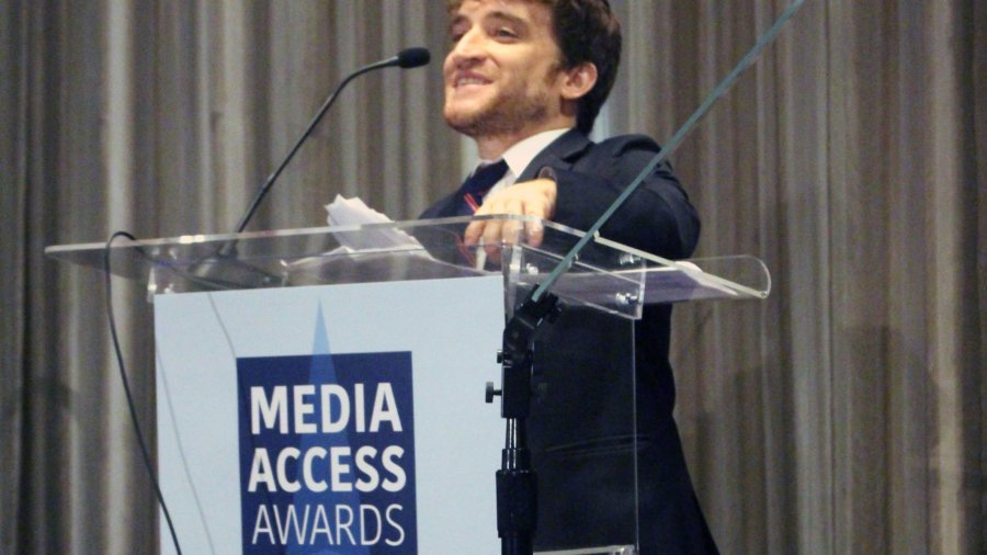 Nic Novicki standing at a podium with the sign Media Access Awards
