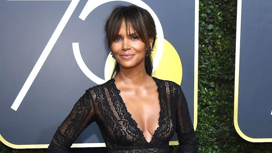 Halle Berry smiling for the camera in a black dress