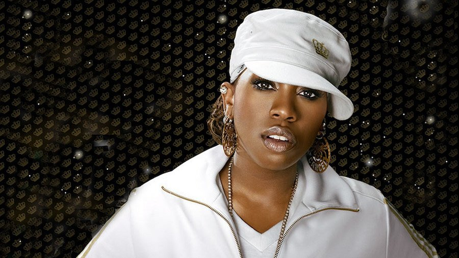 Missy Elliot posting for the camera wearing a white top and hat