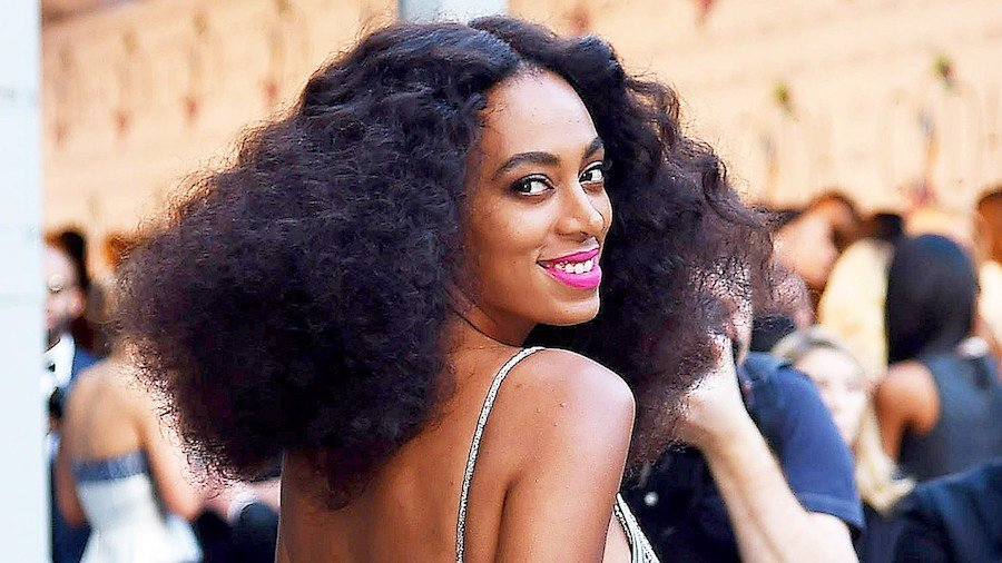 headshot of Solange Knowles wearing a gold dress and pink lipstick