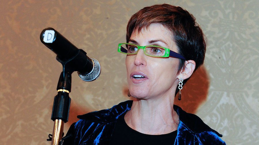 Deborah Calla wearing green glasses behind a microphone