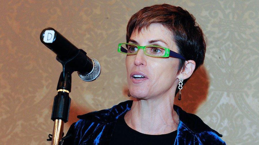 Deborah Calla wearing green glasses behind a microphone