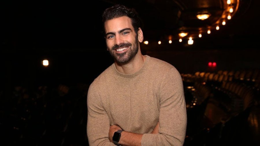 Nyle DiMarco smiling wearing a brown sweater