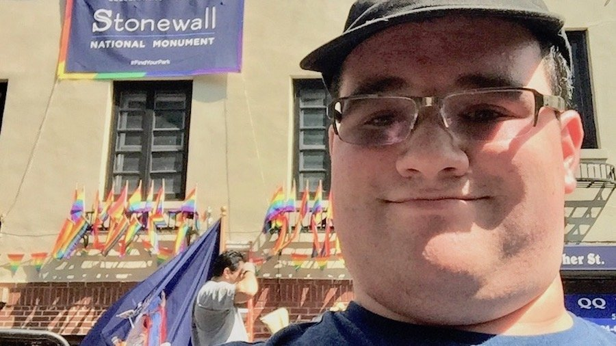 Former RespectAbility Fellow Eric Ascher in front of the Stonewall Inn in New York City with a banner reading