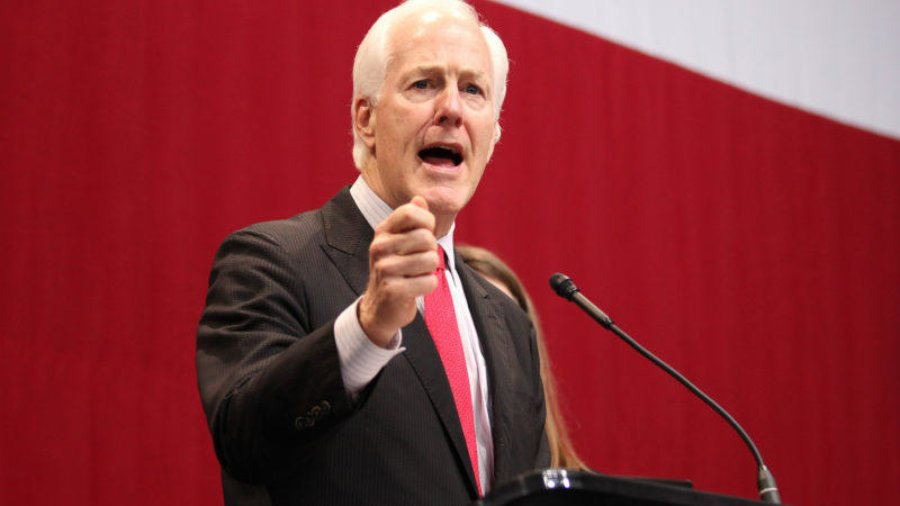 Sen. John Cornyn giving a speech at a podium in front of a red and white background