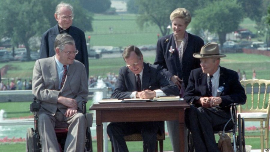 President George H.W. Bush signs the Americans with Disabilities Act into law, surrounded by two wheelchair users and two people standing behind him.