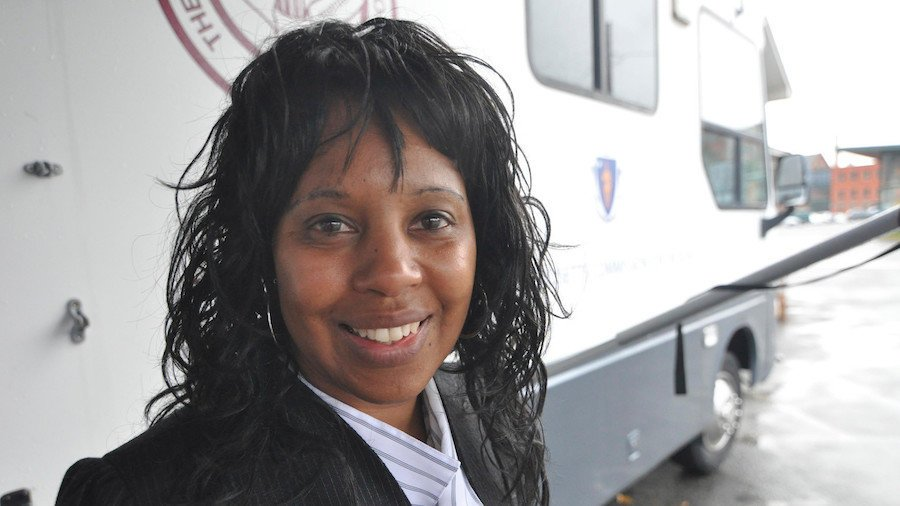 Janet Labreck smiling in front of the New England Eye Mobile Care Clinic