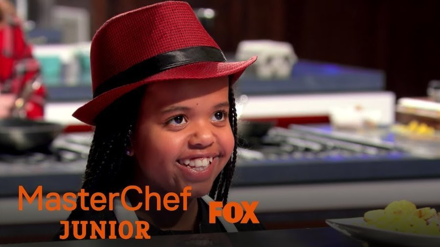 Ivy smiling on MasterChef Junior in the kitchen. Logos for MasterChef Junior and Fox