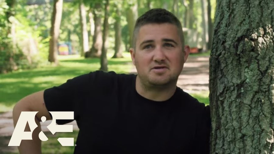 Still from the Employables with one of the featured people leaning against a tree in the woods. A&E Logo in bottom left