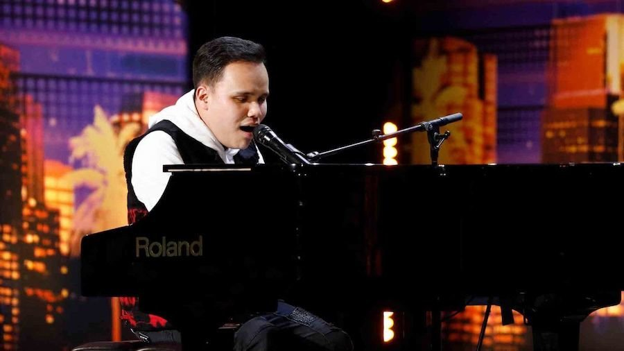 Kodi Lee sitting behind the piano on stage on America's Got Talent, singing