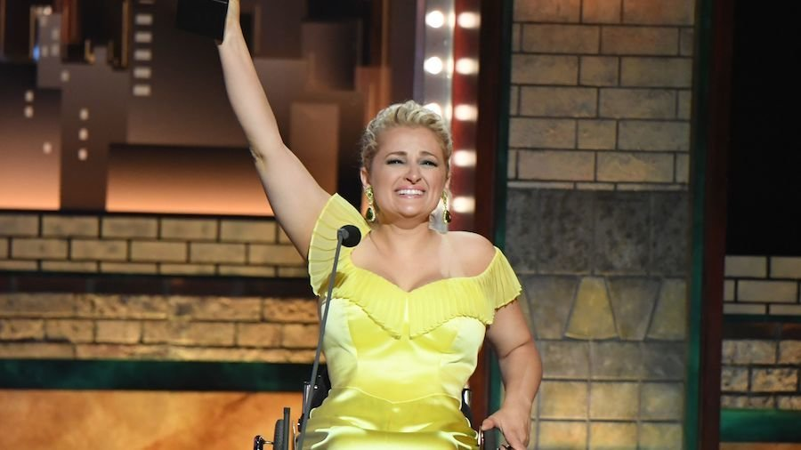 Ali Stroker holds her Tony award in the air on stage at the ceremony