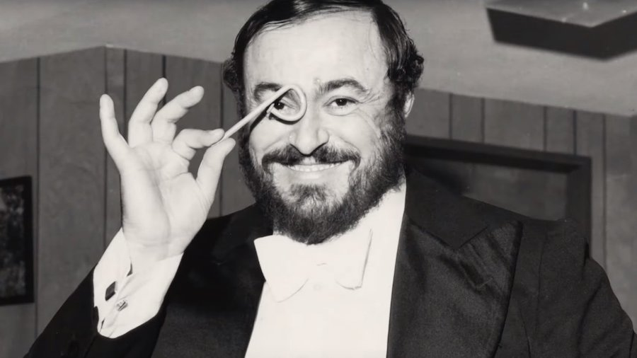 Luciano Pavarotti holding up something in front of his eye, smiling