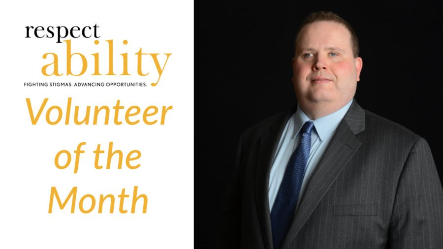 Gary Norman smiling wearing a suit and tie in front of a black background Text: RespectAbility Volunteer of the Month.