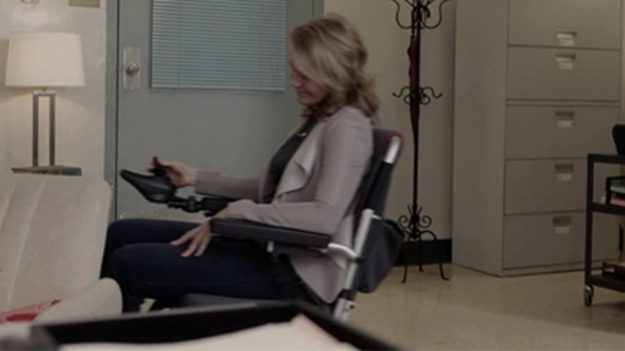Eileen Grubba seated in a wheelchair moving through a room