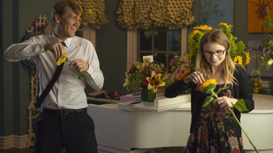 Josht Thomas and Kayla Cromer picking flower petals off of flowers inside a kitchen in a scene from Everything's Gonna Be Okay.