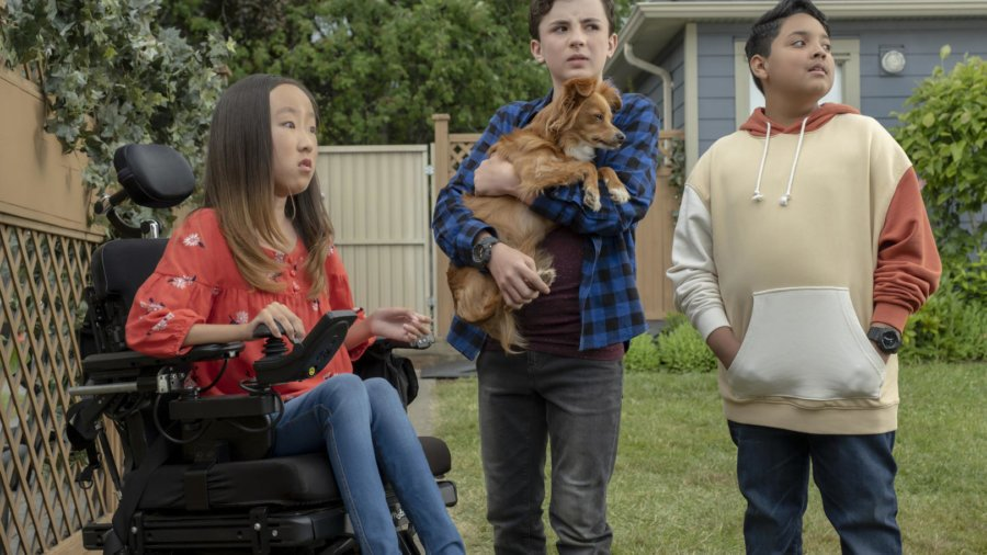 three pre-teens, one girl in a wheelchair, and two boys standing, one holding a dog