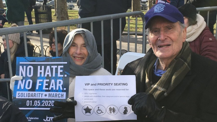 Elderly couple seated at solidarity rally in priority seating section holding signs for the march and the priority seating section